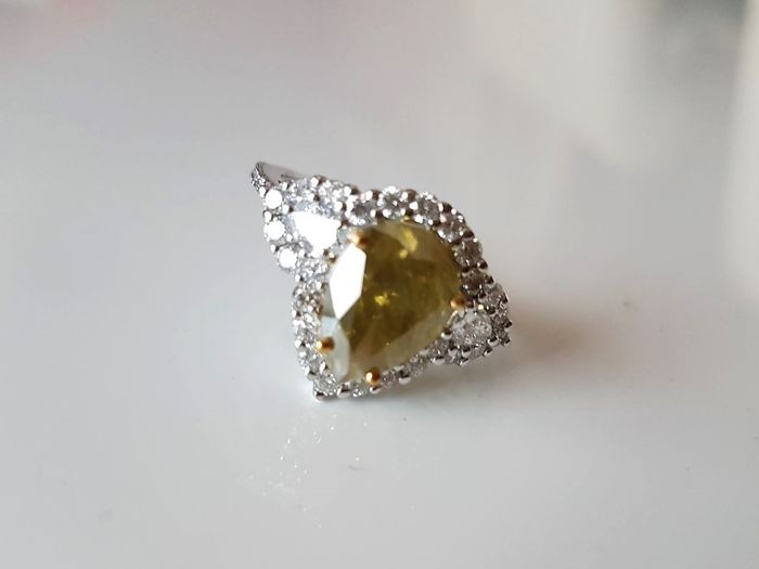 Ring in 18 kt white gold set with a 3.21 ct pear cut diamond, colour grade: fancy deep brownish-greenish-yellow, plus white accent diamonds