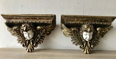 Two large gold-plated wall consoles with angels