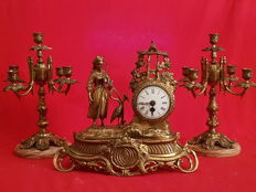 French-style bronze clock with a figure of a woman and a stork, accompanied by two matching candelabra for 5 candles. 20th century