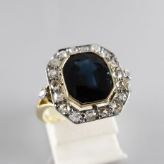 18 kt early Art Deco ring with a central blue sapphire and 20 rose cut diamonds