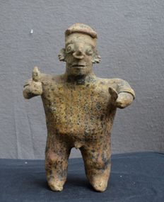 A Pre-Columbian earthenware sculpture - depicting a standing man with rattles - 24.7 cm