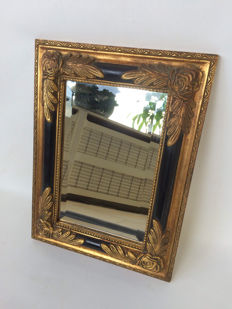 Cut mirror in a black golden frame trimmed with roses, mid 20th century