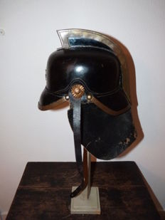 Dutch fire helmet of black leather and brass crest 1880-1940.