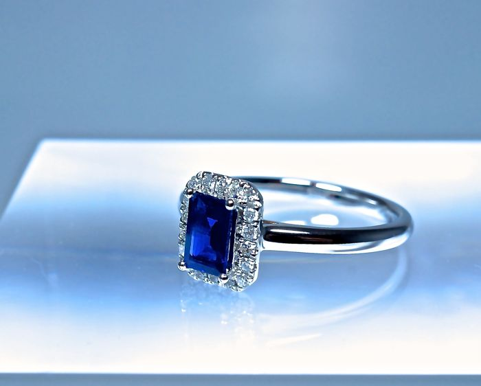 Emerald/baguette cut sapphire of 0.64 ct, certified natural by the IGI laboratory in Antwerp, on an 18 kt rhodium-plated white gold ring with an entourage of diamonds of 0.13 ct
