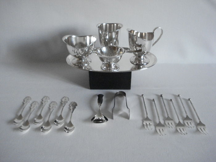 Schoonhoven (Silver city of the Netherlands) by Herbert Hooijkaas  (HH) for Douwe Egberts:  Silver plated items:  Cream set with spoon vase and tea strainers, Empire style. Spoons, Biedermeier. Forks, with twisted hilt with knob.