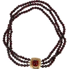 14 kt - Three-strand garnet necklace strung on black thread, fitted with a 14 karat yellow gold box clasp set with a facet cut garnet - Length 35.5 cm