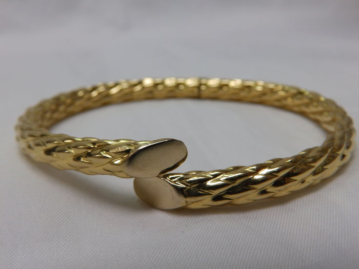 Rrigid oval bracelet, open and adjustable, in two-tone gold.  18 kt.  70 x 60 mm