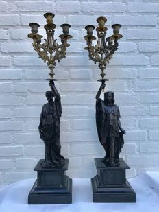 A pair of large bronze candlesticks carried by  Roman / Egyptian figures - 20th century