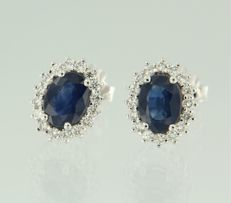 14 kt White gold, entourage ear studs set with a central, oval cut sapphire with an entourage of 32 brilliant cut diamonds, size 1.2 x 1.0 cm