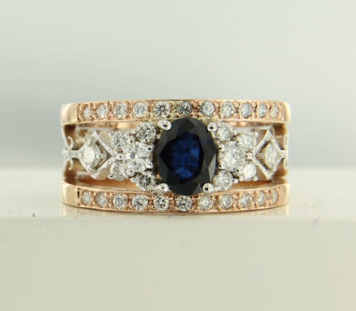 14 kt bi-colour gold ring set with a central 1.20 ct oval facet cut sapphire and an entourage of 34 brilliant cut diamonds, 0.66 ct