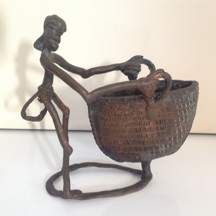 Old bronze African sculpture of a basket carrier