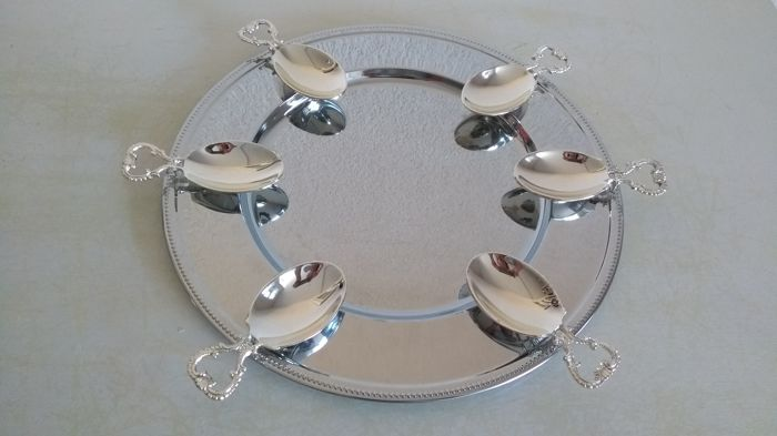 Six decorated amuse spoons on large serving plate with pearl rim.