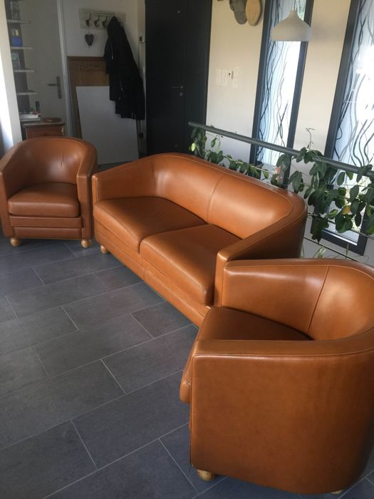 A very nice set in tan leatherette: two club chairs and a sofa from the 1950s/60s.
