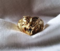 14 kt gold ring in the shape of a lion's head with a sapphire in its mouth