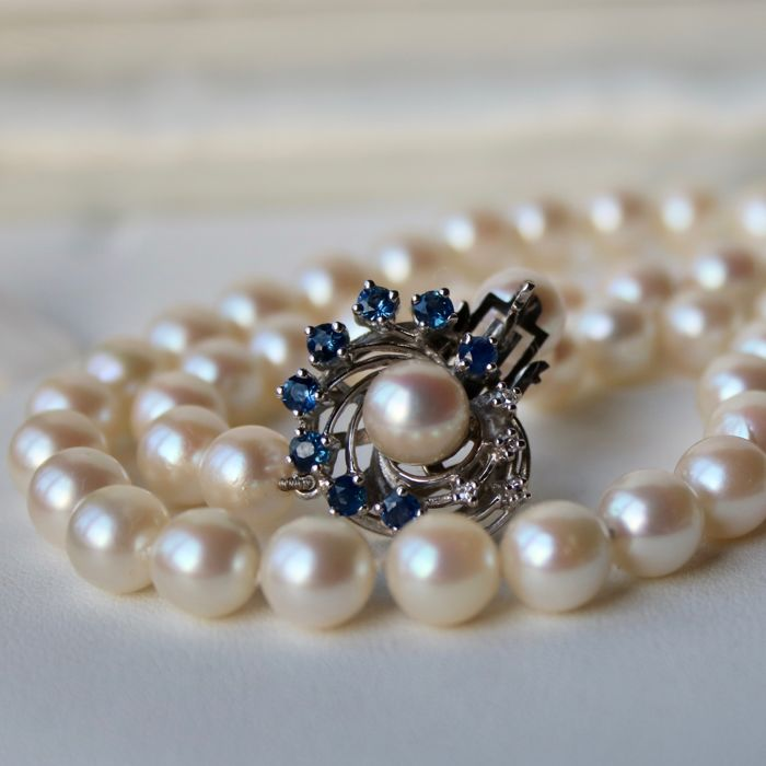 Pearl necklace with natural sea/salty Japanese Akoya in ivory white color with an excellent lustre. 14Kt. White-Gold clasp set with beautiful 8 natural blue Sapphires and 5 diamonds ca. 0.775Ct. Excellent sta
