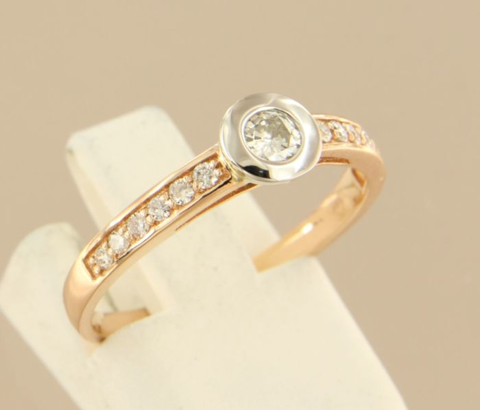 14 kt bi-colour gold ring set with a central 0.18 carat brilliant cut diamond and 12 diamonds, ring size 17.5 (55)