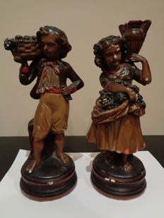 Couple of polychrome sculptures of a child holding a fruit and a girl holding basket of fruit and a vase - France - Beginning of the 20th century