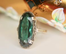 Art Deco  ring in gold and sterling silver with an oval cut green Spinel in a fine decorated setting, ca. 1920