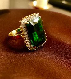 Gold (585) ring with green clear, faceted, synthetic stone in the centre and 28 sapphires or topazes