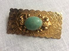 Gold brooch with blue stone