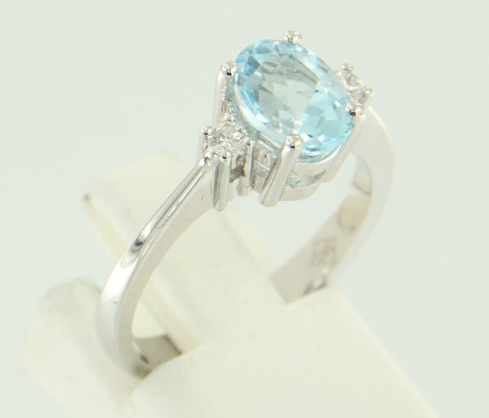 14 kt white-gold ring, set with a blue topaz in the centre and 2 brilliant-cut diamonds of approx. 0.10 ct in total, ring size: 17 (53)