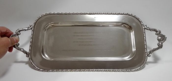 A silver plated serving tray with richly decorated profile edge