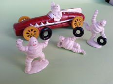 Vintage Michelin man (Bibendum) in race car and a set of three Michelin men having fun