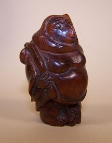 A wooden 'katabori netsuke' shaped as a pot-bellied monkey dressed as a monk - Japan - ca 1925 (Taisho period)