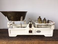 Old balance scale with copper and brass weights.