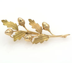 Yellow gold needle brooch shaped like an oak branch.
