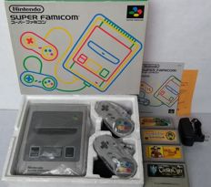 Boxed Super Nintendo console (Japanese import) with universal power supply, 2 controllers  and 4 Japan-exclusive games