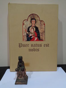 Antique sculpture of Our Lady of Montserrat (Patron saint of Catalonia) and book: Puer natus est nobis. The iconography of Christmas in the Medieval art.