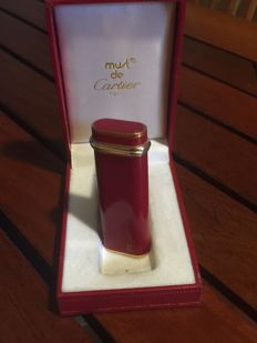 Must de CARTIER : Lighter in red lacquer, three golds, model Trinity in lacquered metal, in its case. Very good condition.