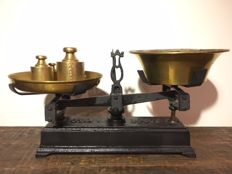 Old cast iron balance scale with copper and weights.