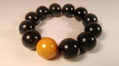 Round Modified black colour Baltic amber bracelet with one Egg yolk colour bead accent, hole ca. 52, 39 grams