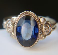 Antique silver ring with a 2.60ct blue Tourmaline on a rose decorated frame.