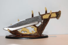Very fine and artfully carved hunting knife on stand