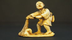 Ivory Netsuke fisherman with an enormous fish in his net, signed on the bottom - Japan - 1900 (Meiji period)