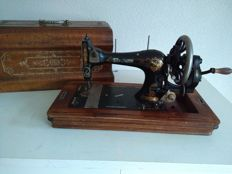 Antique manual sewing machine, decorated with golden engravings and the original wooden cover / key