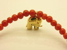 Bracelet consisting of red Mediterranean coral beads with an 18 kt gold elephant lucky charm