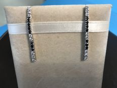 A pair of 18 kt white gold matchstick dangle earrings with diamonds and black agates, with a total carat weight of 1.36 ct