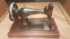 Singer manual sewing machine with a wooden dust cover