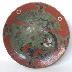 Large stoneware dish with a decoration of a bird in a garden - Japan - mid 20th century