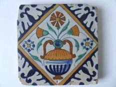 "Antique tile with a coloured flower vase in a square and ""spaartechniek"" corners"