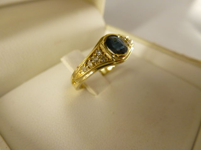 18 kt gold ring with blue sapphire and 0.20 ct diamonds.