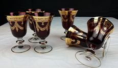 Set of six ruby-red crystal wine chalices with golden decorations