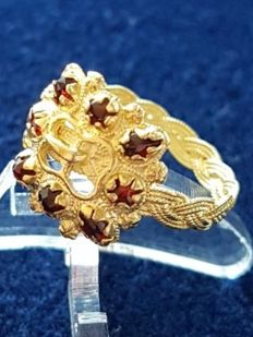Stunning rare buckle ring made of 22 karat yellow gold set with rose cut garnets and a finely braided band 17th/18th century