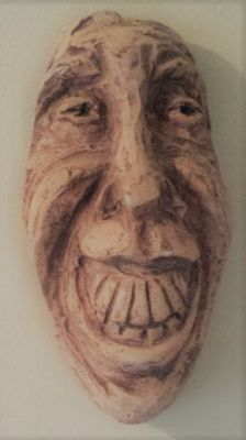 terracotta mask.  Piece of hanging on the wall .