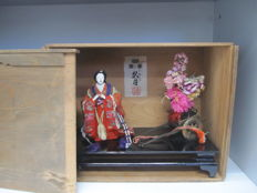 A set of a large ningyo doll presenting a woman and her flowers filled cart,  box with kyugetsu house seal - Japan - 1st half 20th