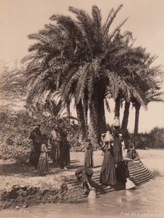 Gabriel Lekegian (active circa 1887-1925) Palm trees and water carrier by the Nile, Egypt